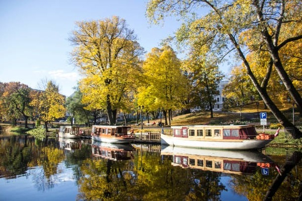 tourist boats Autumn park in the center of Riga, Latvia Canal that flows through Bastion park autumn background with colored leaves (Bastejkalns)..