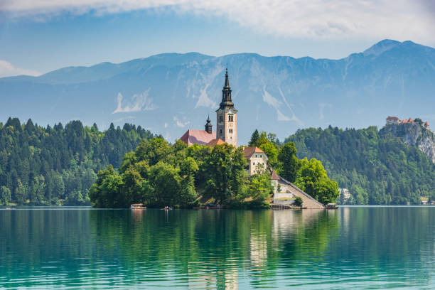 Beautiful Lake Bled in Slovenia. 'Church dedicated to the Assumption of Mary' - Santa Maria Church with surrounding houses and clock tower in the middle of small islet in the famous slovenian lake. Alps in the background. Lake Bled, Slovenia, Europe