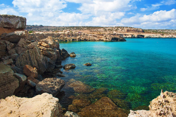 Image of Blue Lagoon bay near Cape Greco, Cyprus. View of rock coastline near deep green transparent emerald water against a rocky hill. Amazing cloudscape. Warm day in fall