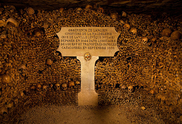 Piles of bones and skulls are arranged into a stack in the Paris' Catacombs.