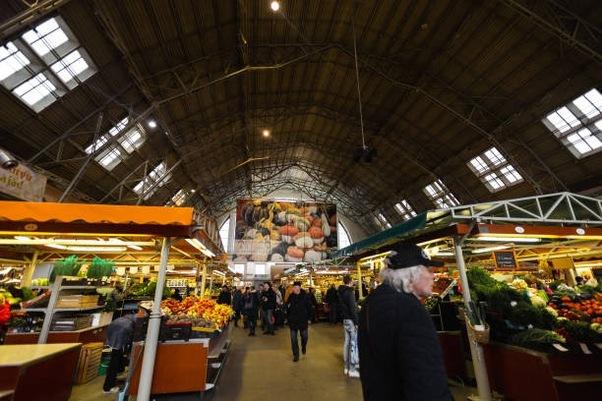 RIGA, LATVIA - MARCH 16, 2019: Riga Central market pavilion, people buying food - Former zeppelin hangars - Rigas Centraltirgus
