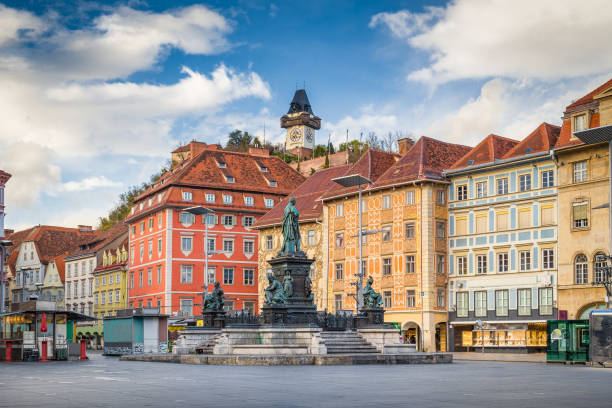 Classic view of the historic city of Graz with main square and famous Grazer clock tower in the background sitting on top of Schlossberg hill, Styria, Austria