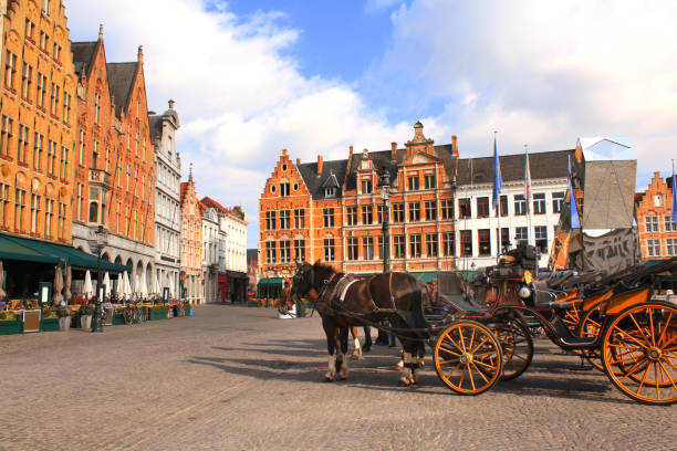 Old houses and horse carriages on Grote Markt square, medieval city Brugge, Belgium, Europe. UNESCO world heritage site