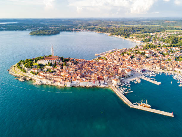 Croatian town of Rovinj on a shore of blue azure turquoise Adriatic Sea, lagoons of Istrian peninsula, Croatia. High bell tower, red tiled roofs of historical buildings, sailboat, piers. Aerial view.