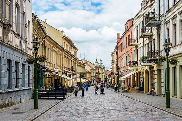 Kaunas, Lithuania - June 22, 2015. Walking tourists, gas lanterns and historic buildings in Old town.