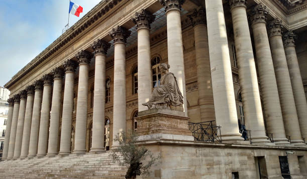 The classic buuilding with columns now the Bourse with French flag flying in the Marais district Paris France
