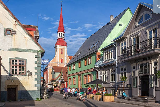 Pärnu, Estonia - July 20, 2016: A street lined with wooden buildings in central Pärnu. In the background is the 18th century St Elizabet's Church, a landmark in the city.