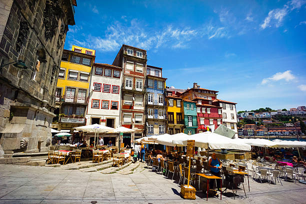 Porto, Potugal - June 11, 2015: Tourists visit restaurants at famous place Ribeira Square at day time