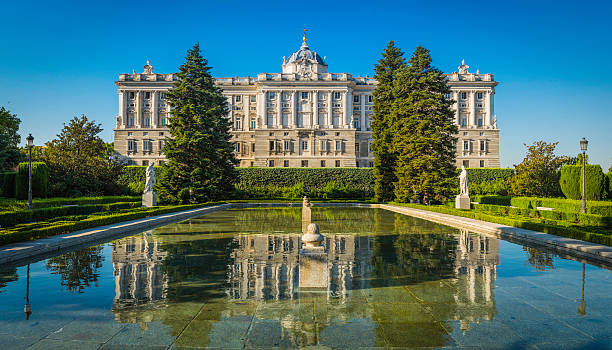 The historic facade of the Palacio Real reflecting in the still waters of the ornamental pond set amongst the green trees of the Sabatini Gardens in the heart of Madrid, Spain's vibrant capital city. ProPhoto RGB profile for maximum color fidelity and gamut.