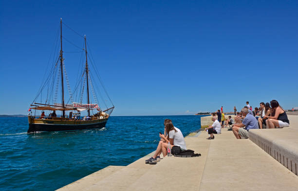 Zadar, Croatia - June 18th 2016. Tourists watch the boats go by as they listen to the Sea Organ (Morske Orgulje) on zadar's waterfont. This experimental musical instrument plays music through the movement of sea waves and tubes positioned under the steps.