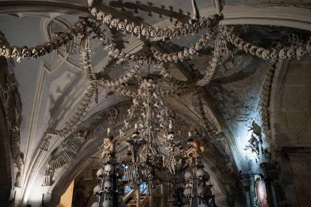 """Kutna Hora, Czech Republic - November 11, 2018: Ceiling at Cemetery Church of All Saints """"ornamented"""" with Human bones and skulls in the Ossuary at Kutna Hora, Czechia"""