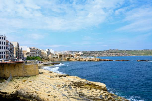 View along St Pauls Bay waterfront and rocky coastline with apartments to the left and people going enjoying the setting, Bugibba, Malta, Europe.