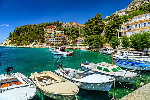 Typical mediterranean houses and fishing harbor with motorboats,Makarska riviera,Brela,Dalmatia,Croatia,Europe