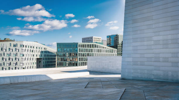 Oslo, Norway - September 15, 2019: Panorama detail of the famous Modern Architecture Opera House - Operahuset with urban Cityscape View of Oslo in the background. Modern Architecture under blue sunny late summer skyscape. Oslo, Norway, Scandinavia, Europe.